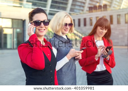 Portrait of a business woman talking on the mobile phone. Friends group women watching the smart phone outdoor.  - stock photo