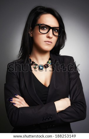 Portrait of a business woman with eyeglasses wearing stylish clothing, jewelery, accessories, and arms crossed. - stock photo