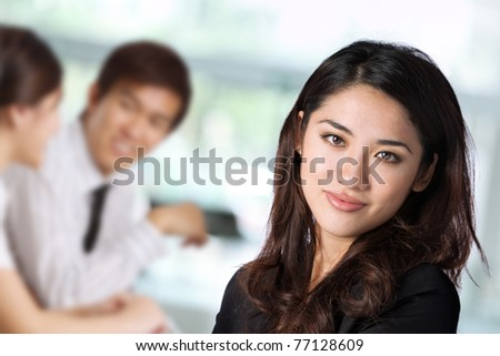 Portrait of a business woman with her colleagues in the background - stock photo