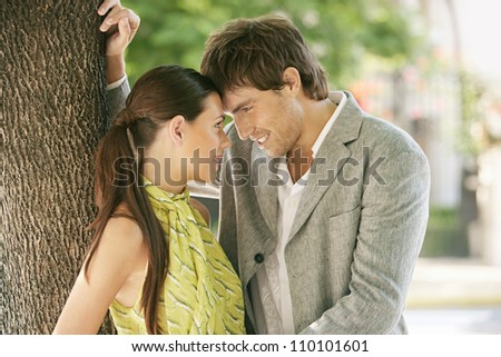 Portrait of a businessman and a businesswoman being affectionate and holding their foreheads together while leaning on a tree outdoors. - stock photo