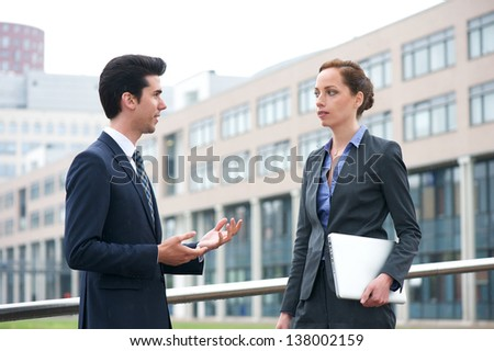Portrait of a businessman and business woman in discussion out of the office - stock photo