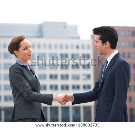 Portrait of a businessman and business woman shaking hands - stock photo