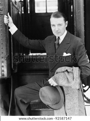 Portrait of a businessman boarding a train - stock photo