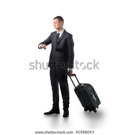 Portrait of a businessman carrying a suitcase and looking at his watch - stock photo