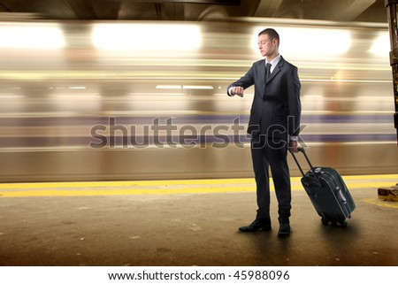 Portrait of a businessman carrying a suitcase and looking at his watch on an underground platform - stock photo