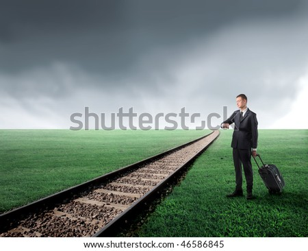 Portrait of a businessman carrying a suitcase and standing next to a railway running through a green meadow - stock photo
