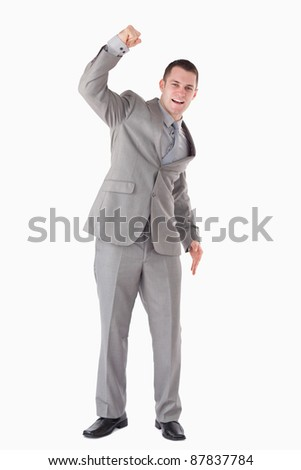 Portrait of a businessman cheering up against a white background