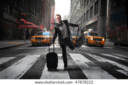 Portrait of a businessman crossing quickly a city street with a suitcase in his hand