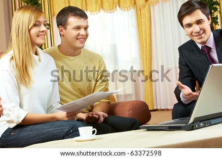 Portrait of a businessman explaining something in laptop to young couple