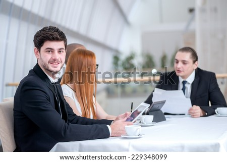 Portrait of a businessman. Four confident successful businessmen at a meeting while sitting at a table discussing business case in the office on laptop - stock photo