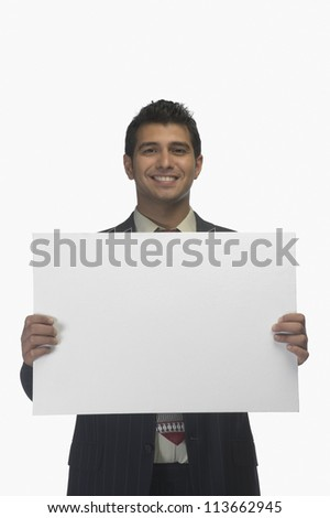 Portrait of a businessman holding a blank placard and smiling - stock photo