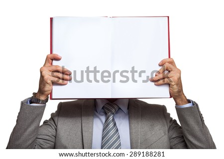 Portrait of a businessman holding a book in front of his face - stock photo