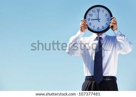 Portrait of a businessman holding a clock against blue background - stock photo
