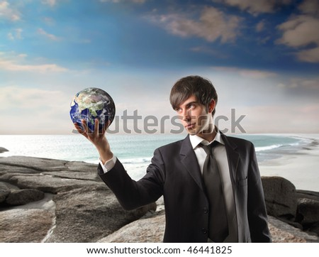 Portrait of a businessman holding a globe in his hands with seascape on the background - stock photo