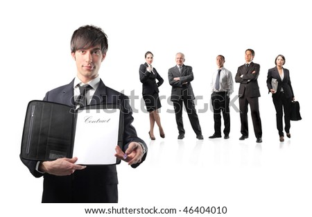 Portrait of a businessman holding a non-signed contract and a pen with a business team on the background - stock photo