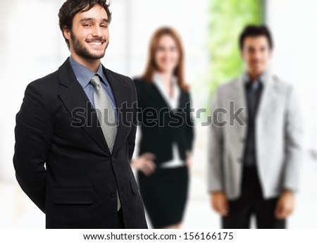 Portrait of a businessman in front of his team - stock photo