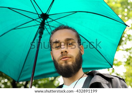 Portrait of a businessman in the park during rainy season. Man looking at camera. View from below.  - stock photo