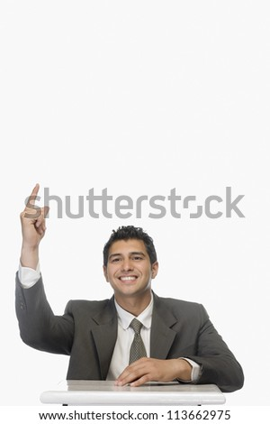 Portrait of a businessman indicating upward and smiling - stock photo