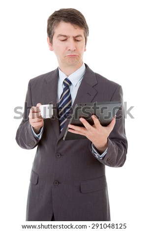 Portrait of a businessman looking at tablet pc and holding cup of coffee, isolated - stock photo
