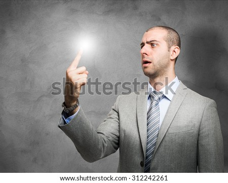 Portrait of a businessman looking surprised at his lighten-up finger - stock photo