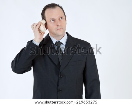 Portrait of a businessman, mature, bald, wearing a suit and tie, holding a seashell next to your ear, with a worried face on white background - stock photo