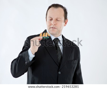 Portrait of a businessman, mature, bald, wearing a suit and tie, holding a small boat and looking at him on white background - stock photo