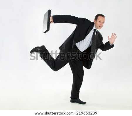 Portrait of a businessman, mature, bald, wearing a suit and tie, the whole body, with a briefcase and running on a white background - stock photo