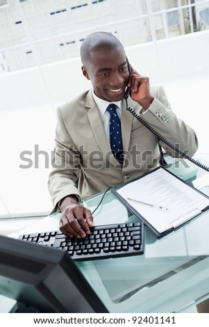 Portrait of a businessman on the phone in his office - stock photo