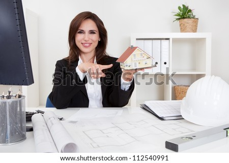 Portrait of a businessman pointing at home model with blueprints on office desk - stock photo