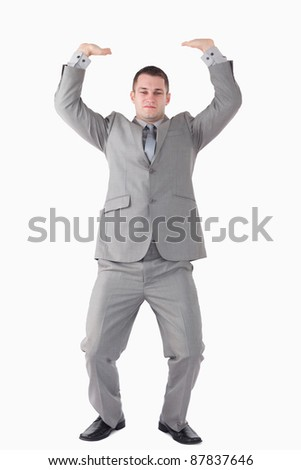 Portrait of a businessman pushing the roof against a white background - stock photo