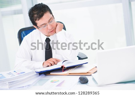 Portrait of a businessman reading at office - stock photo
