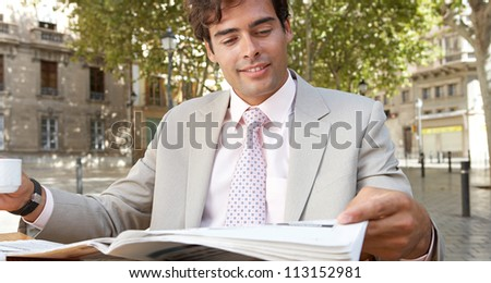 Portrait of a businessman reading the newspaper having drinking coffee in a coffee shop terrace, smiling.