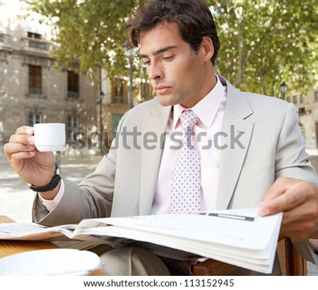 Portrait of a businessman reading the newspaper while drinking coffee in a coffee shop terrace, outdoors. - stock photo