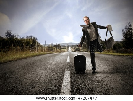 Portrait of a businessman running on a countryside road and carrying some bags - stock photo