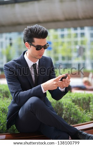 Portrait of a businessman sending message on his phone outdoors - stock photo
