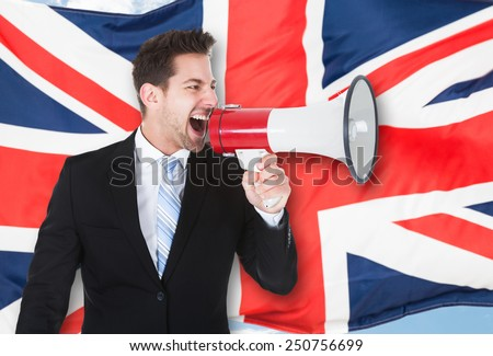 Portrait Of A Businessman Shouting Through Megaphone In Front Of British Flag - stock photo