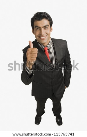 Portrait of a businessman showing thumbs up sign and smiling - stock photo