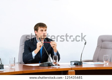 Portrait of a businessman sitting at a table and holding a pen - stock photo