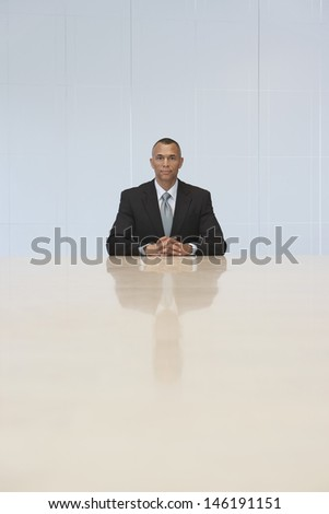 Portrait of a businessman sitting at the end of conference table in office - stock photo