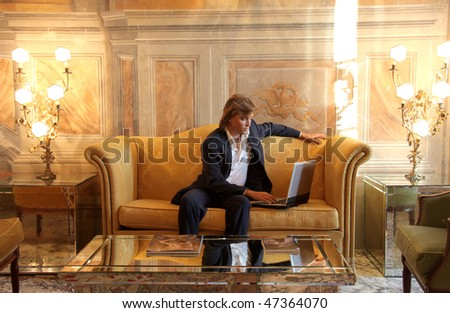 Portrait of a businessman sitting in a sofa in a luxury hotel and working on a laptop - stock photo