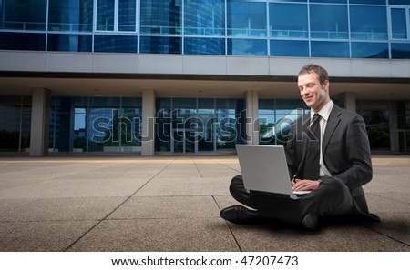 Portrait of a businessman sitting in front of a building and using a laptop - stock photo