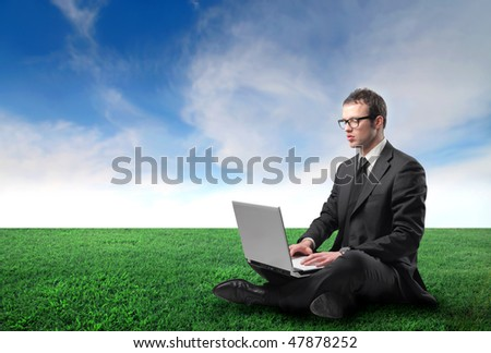 Portrait of a businessman sitting on a green meadow and using a laptop - stock photo