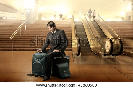 Portrait of a businessman sitting on his luggage in the middle of an airport hall - stock photo