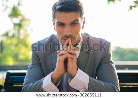 Portrait of a businessman sitting on the bench outdoors and thinking - stock photo