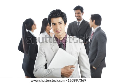 Portrait of a businessman smiling with his colleagues in the background