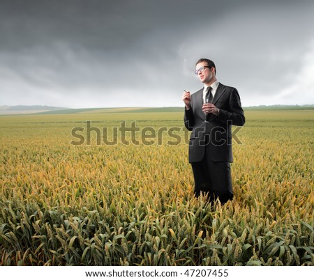Portrait of a businessman smoking a cigarette on a cornfield - stock photo