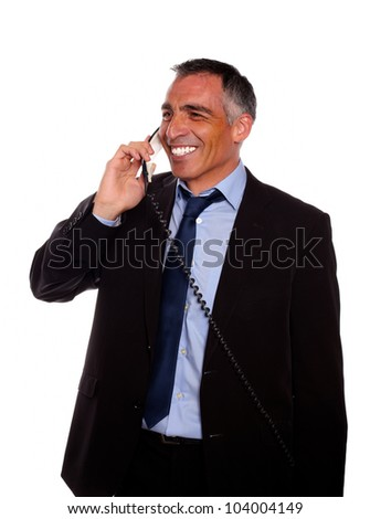 Portrait of a businessman speaking on phone while looking to right and wearing a black suit against white background - stock photo