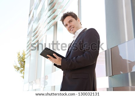 Portrait of a businessman standing by a modern architecture glass office building in the city, using a technology smart tablet pad, smiling. - stock photo