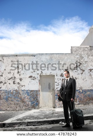 Portrait of a businessman standing in front of an ancient building and carrying a suitcase - stock photo