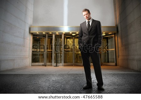 Portrait of a businessman standing in front of the entrance of a building - stock photo